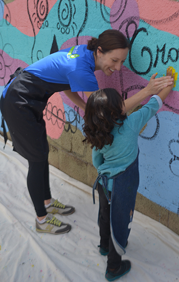 Free Arts mentor helps a child paint a mural.   PHOTO COURTESY FREE ARTS